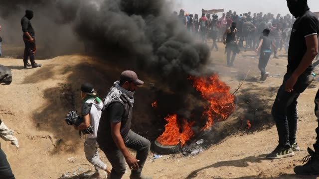 palestinians burn tires near the border fence with israel as mass demonstrations at the fence continue on may 11 2018 in gaza city gaza one man was... - 2018 gaza border protests stock videos & royalty-free footage