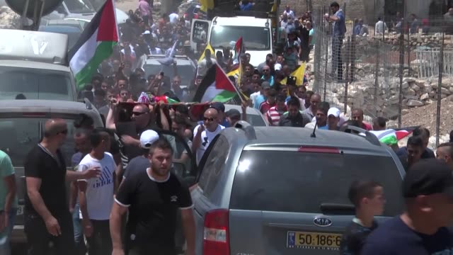 palestinians carry the body of 12 year-old mouhey tabakhi next to the separation barrier during his funeral at the west bank town of al-ram on july... - grief stock videos & royalty-free footage
