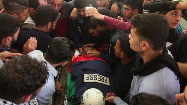 palestinians carry the body of palestinian journalist ahmad abu hussein during his funeral in jabaliya refugee camp in the northern gaza strip 26... - arabien stock-videos und b-roll-filmmaterial