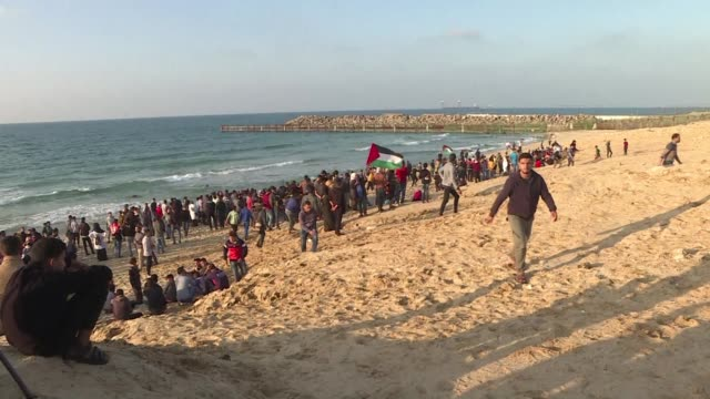 Palestinians evacuate injured protesters and throw stones using slingshots during protest at the border in Beit Lahia between Gaza and Israel