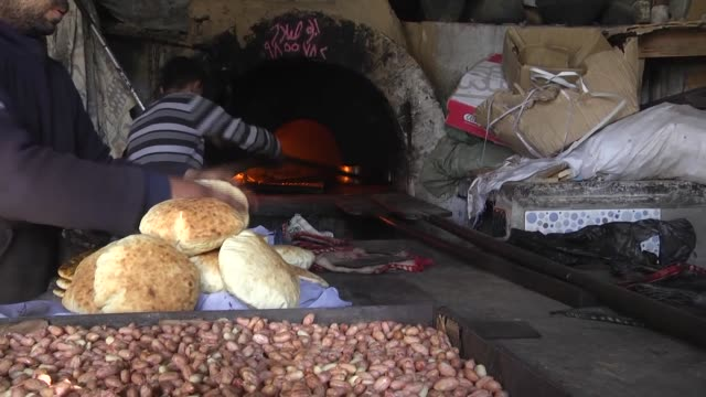palestinians gather at a stone oven to cook their food and buy bread, in gaza, gaza city on january 19, 2017. palestinians cook their food at a stone... - gaza city stock videos & royalty-free footage