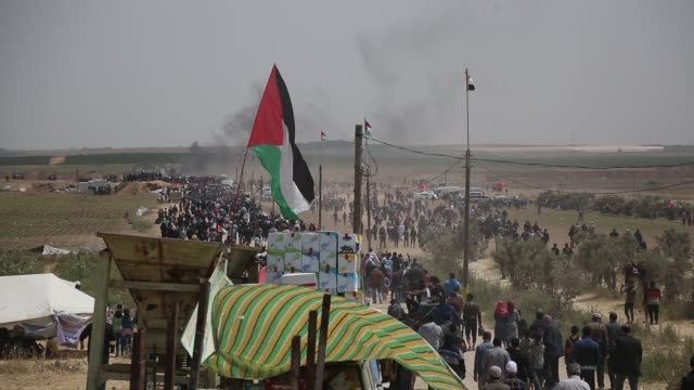 palestinians gather to protest near the israeli border fence, east of gaza city in the central gaza strip on april 13, 2018. several thousand gazans... - 2018 gaza border protests stock videos & royalty-free footage