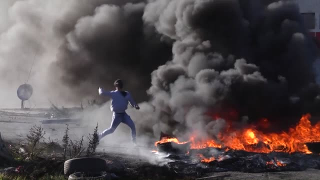 palestinians, gathered in beyt eil check point to protest israel's violations, burn tires and sling stones to israeli soldiers in ramallah, west bank... - イスラエルパレスチナ問題点の映像素材/bロール