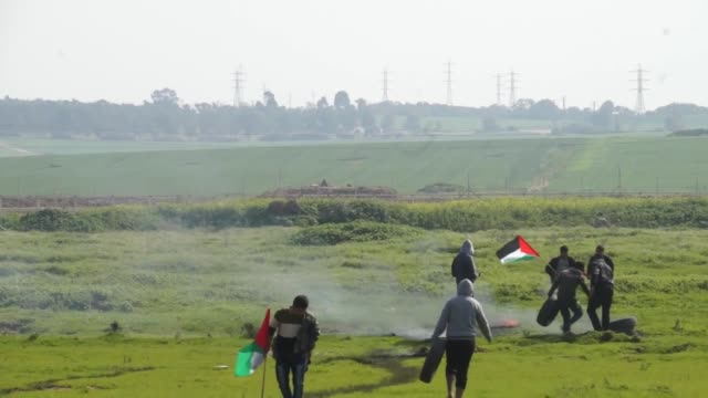 palestinians hold a protest demanding the reconstruction of gaza and lifting of israeli blockade on gaza strip on february 09 2015 near the border... - israelisches militär stock-videos und b-roll-filmmaterial