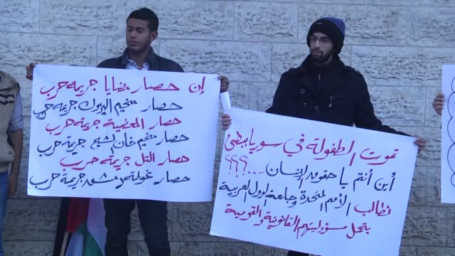 palestinians hold flags and carry placards during a protest for civilians who starved to death in madaya in front of international committee of the... - ausgemergelt stock-videos und b-roll-filmmaterial