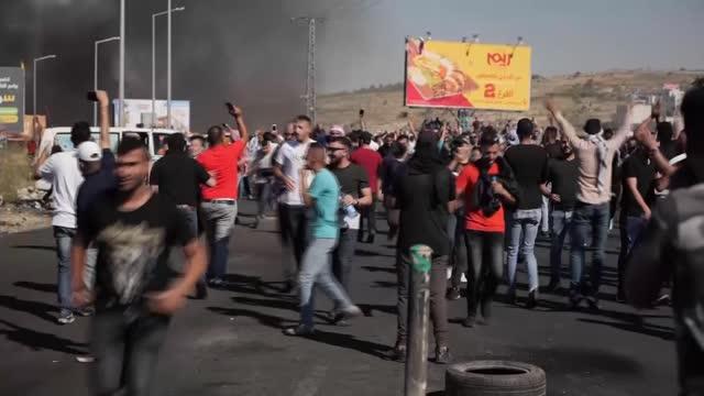 palestinians hold general strike as israeli airstrikes and hamas rocket attacks continue; west bank: ramallah: ext rear view man waving flag gv woman... - shaky stock videos & royalty-free footage