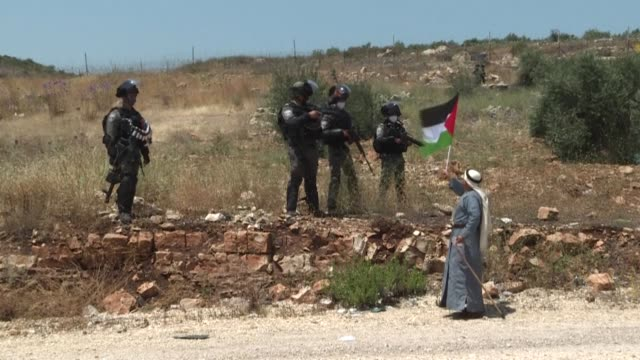 palestinians in the west bank city of tulkarem wave palestinian flags and chant slogans during a demonstration to mark 53 years of israeli occupation... - israel palestine conflict stock videos & royalty-free footage
