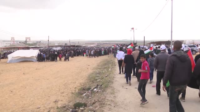 palestinians injured by israeli army gunfire on march 30, 2018 near the gaza strip's eastern border with israel, are carried by other protesters... - 2018年ガザ地区国境抗議点の映像素材/bロール