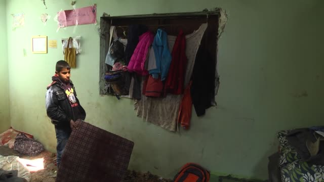 Palestinians inspect a bedroom of a house damaged in the Israeli air attacks which killed 10yearold boy Yassin Abu Khousa and injured his two...
