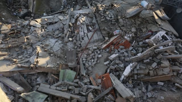 palestinians inspect the rubble of a hamasrun insurance office after it was destroyed by an israeli air strike in gaza city march 26 2019 israel... - luftangriff stock-videos und b-roll-filmmaterial