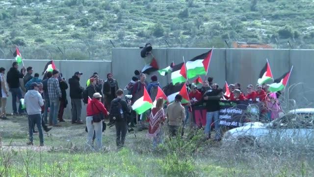vídeos de stock, filmes e b-roll de palestinians march towards israel's controversial separation wall between the west bank village of bilin near ramallah and the israeli settlement of... - ramallah