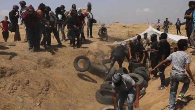 palestinians prepare to burn tires near the border fence with israel as mass demonstrations at the fence continue on may 11 2018 in gaza city gaza... - 2018 gaza border protests stock videos & royalty-free footage