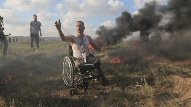 palestinians run away from tear gas fired by israeli forces to disperse palestinians taking part in the great march of return demonstration near... - 2018 gaza border protests stock videos & royalty-free footage