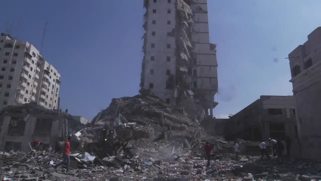 palestinians stand around the debris of tower after israel forces bomb 15-storey basha tower, containing apartments and offices, in gaza city, gaza... - tower stock videos & royalty-free footage