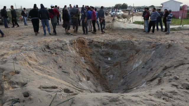 Palestinians stand near damaged remains of a motorcycle and a crater at the area that was reportedly hit by an Israeli strike according to the...