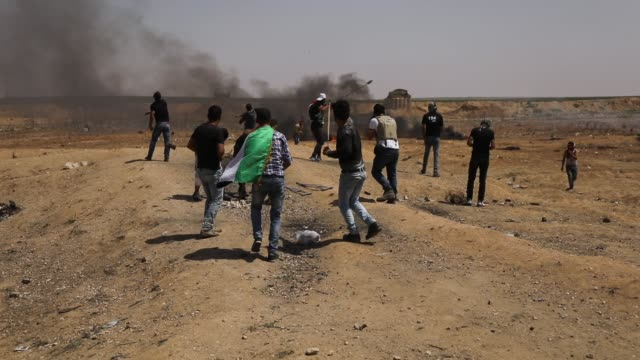 palestinians throw rocks toward the border fence with israel as mass demonstrations at the fence continue on may 11 2018 in gaza city gaza one man... - 2018 gaza border protests stock videos & royalty-free footage