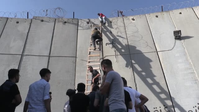 Palestinians use a ladder to climb over the Israeli separation wall in ALRam north of Jerusalem on their way to AlAqsa mosque in the Old city of...