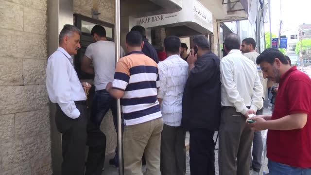 palestinians wait in queue in front to withdraw their salaries from atms in gaza on may 10 2017 the ramallahbased palestinian government has failed... - family with four children stock videos and b-roll footage