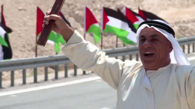 palestinians wave national flags during a protest along a highway leading to the village khan al-ahmar a palestinian bedouin village slated by israel... - palestinian stock videos & royalty-free footage