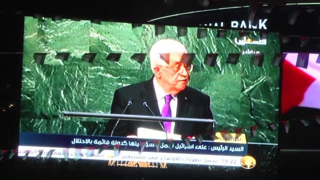 palestinians wave their national flags as they watch a livescreening of president mahmoud abbas' speech followed by the raising of the palestinian... - palestinian flag stock videos & royalty-free footage