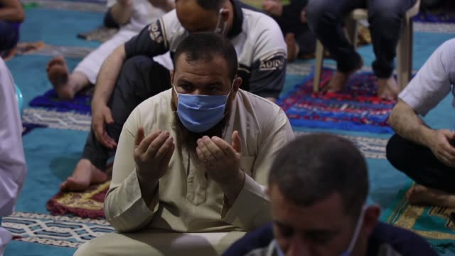 vidéos et rushes de palestinians wearing masks attend friday prayers in a mosque as the holy places reopen to worshippers to perform the weekly islamic ritual, amid... - fidèle religieux