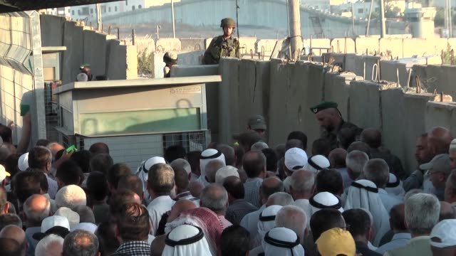 palestinians who want to visit al-aqsa mosque on the islamic holy fasting month of ramadan, enter jerusalem from the kalandia checkpoint with the... - 税関点の映像素材/bロール