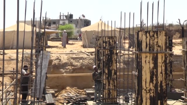 palestinians work on a construction site to rebuild their houses which were destroyed during last summer's war in shujaiyyah neighborhood of gaza on... - rebuilding stock videos & royalty-free footage