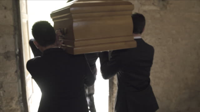 pallbearers leaving church with coffin followed by family - 棺点の映像素材/bロール