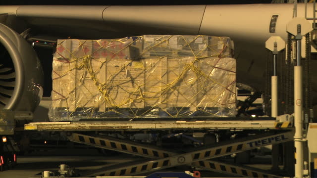 cu pallets being loaded into cargo hold of airbus a380 at night, london, united kingdom - loading stock videos & royalty-free footage