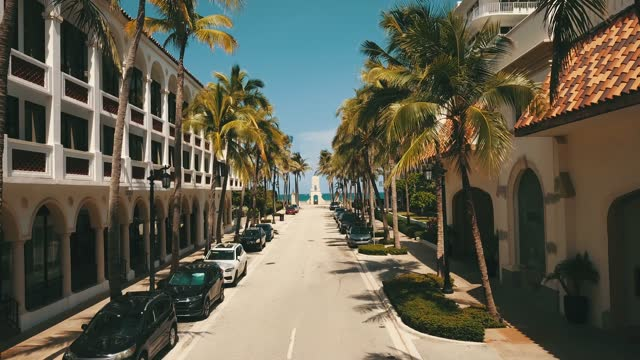 palm beach aerial views of the worth avenue clock tower, waterfront housing, & shadows of palm trees overlooking the beach shore of palm beach, florida during the hot summer in july of 2021 during the rise of the covid-19 delta variant - clock tower stock videos & royalty-free footage
