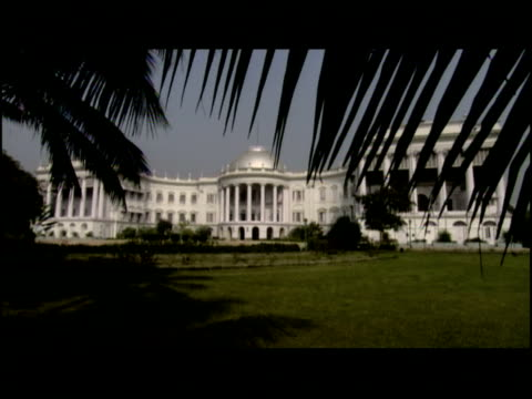 palm fronds frame the kolkata palace and government building. - kolkata stock videos & royalty-free footage