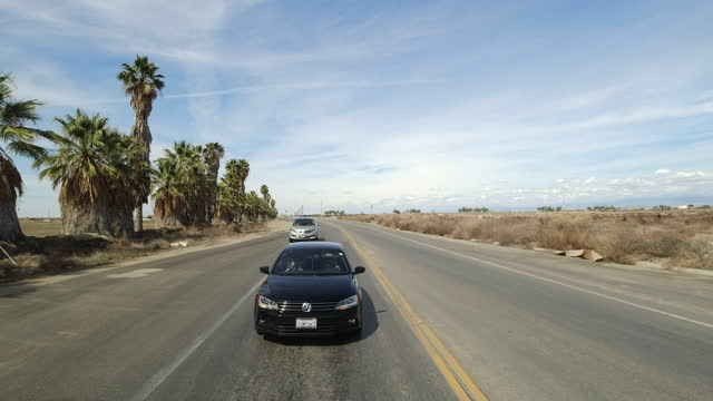 palm tree and rural highway traffic in california in the spring of 2021. - tropical tree stock videos & royalty-free footage
