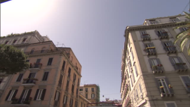 palm trees and large apartment buildings line a street in naples. - ナポリ点の映像素材/bロール