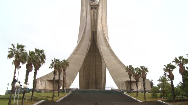 palm trees frame the monument of the martyrs in algiers. available in hd. - アルジェリア点の映像素材/bロール