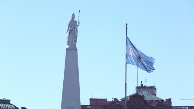 Palm trees Piramide de Mayo Argentina flag moving in breeze on flag pole birds flying Casa Rosada roof BG