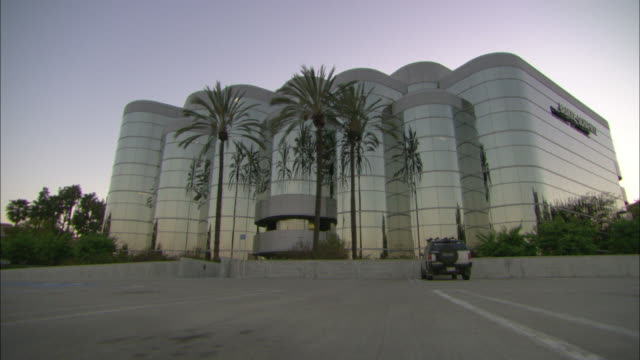 Palm trees wave in the wind in front of a glass building and an almost empty parking lot.