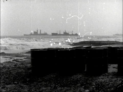 SPAIN SPAIN Palomares GV Wilcon camp BV Men with oil drums two men stand MS Oil drums on beach ships in b/g LS Ships rough sea breaking MS Crane CMS...