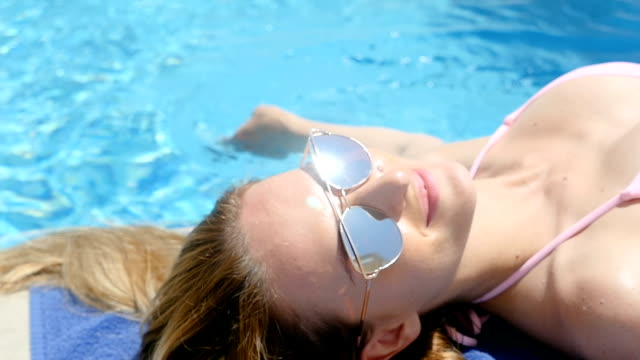 pampering & relaxation by pool - lying on back stock videos and b-roll footage