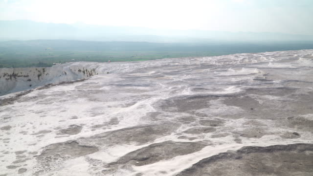 pamukkale pools without flowing water, droughts, and small village in summer. panning view on layers of travertines form terraces of carbonate minerals in pamukkale, natural landmark of natural phenomena at southwest turkey. - natural landmark stock videos & royalty-free footage