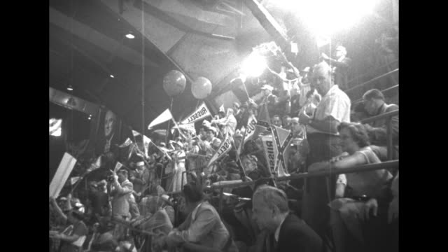 Pan WS 1952 Democratic National Convention hall at the International Amphitheatre crowds standing waving signs / MS from above delegates with signs...