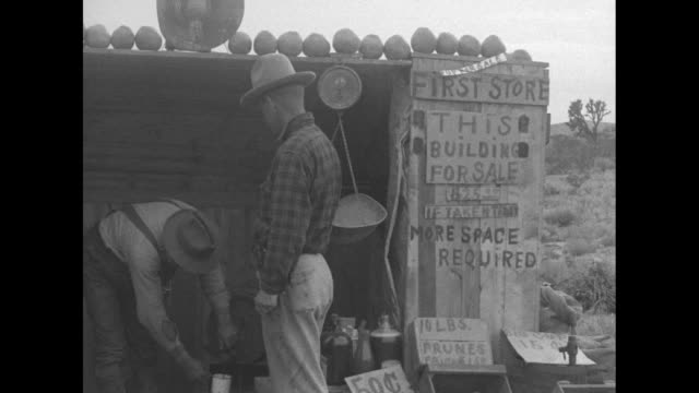 pan about 20 parked cars near tent / vs makeshift shack store with bins of potatoes some kind on produce on top of store / men walk up to store and... - 1926 stock videos & royalty-free footage