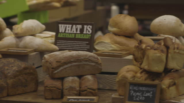 Pan across a table of speciality breads at a supermarket in the UK.