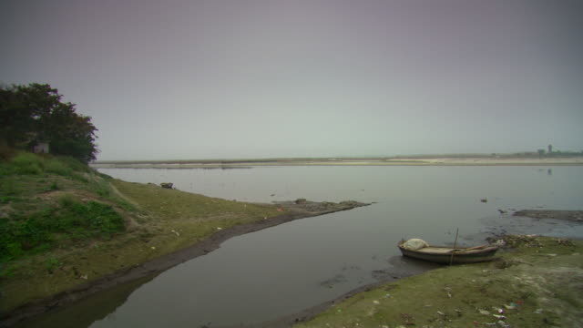 pan across a tributary flowing into the ganges near the city of kanpur.  - estuary stock videos & royalty-free footage