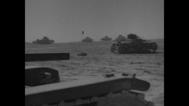 vídeos de stock, filmes e b-roll de vs pan across abandoned italian tanks in desert / two allied soldiers operate abandoned italian antiaircraft gun / soldiers standing on and near... - carro blindado