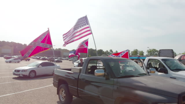 pan across american and confederate flags in parking lot ahead of rally, wide shot - jackson stock videos & royalty-free footage