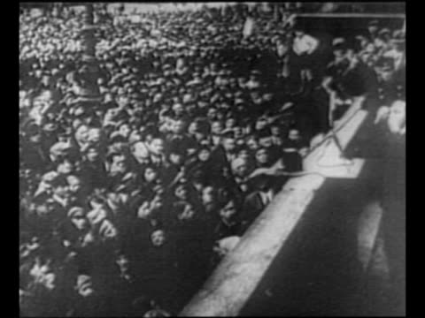 pan across audience of people to joseph goebbels addressing them in foreground as germany's campaign of anti-semitism begins / crowd saluting / army... - 反ユダヤ主義点の映像素材/bロール