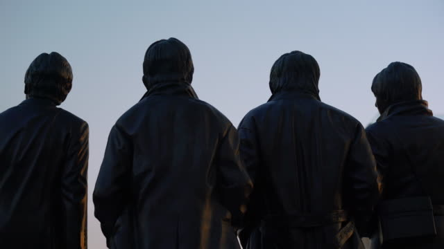 pan across backs of the beatles statue at sunset - liverpool england stock videos & royalty-free footage