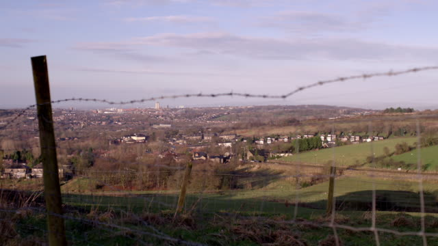 pan across barbed wire fence to manchester - urban sprawl stock videos & royalty-free footage