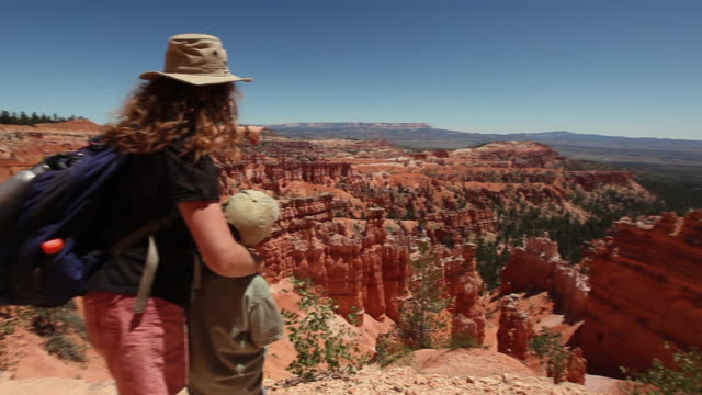 Pan across Bryce Canyon to reveal a hiker mother pointing to view with her son