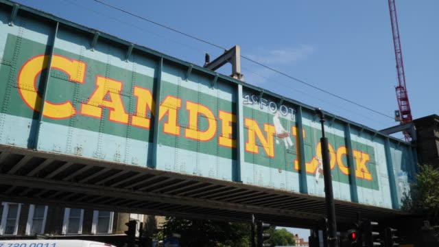Pan across Camden Lock railway bridge with colourful street art